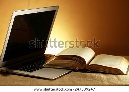 Education concept. Open laptop with blank screen near old book - stock photo