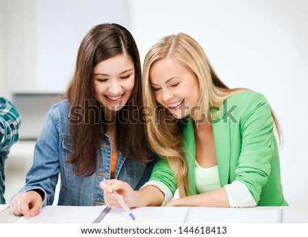 education concept - student girls pointing at notebook at school - stock photo