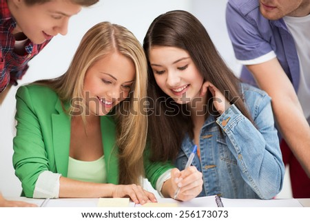 education concept - students pointing at notebook at school - stock photo