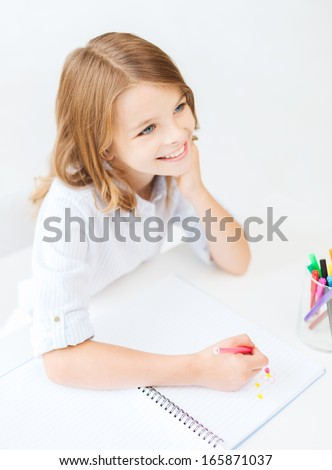 education, creation and school concept - smiling little student girl drawing and daydreaming at school - stock photo