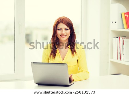 education, e-learning and technology concept - smiling student with laptop computer at school - stock photo