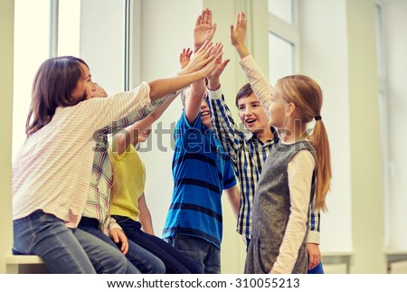 education, elementary school, children, gesture and people concept - group of smiling school kids making high five in corridor - stock photo