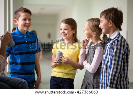 education, elementary school, drinks, children and people concept - group of school kids with soda cans talking in corridor - stock photo