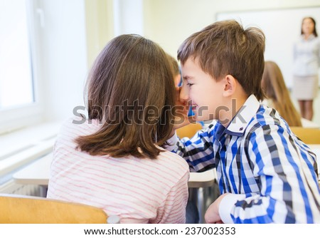 education, elementary school, learning and people concept - smiling schoolgirl whispering secret to classmate ear in classroom - stock photo