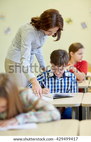 education, elementary school, learning and people concept - teacher helping school boy writing test in classroom - stock photo