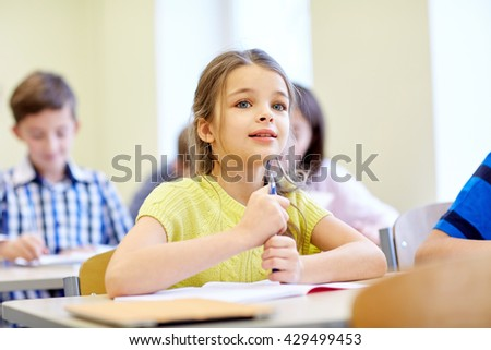 education, elementary school, learning, children and people concept - student girl with group of classmates on lesson in classroom - stock photo