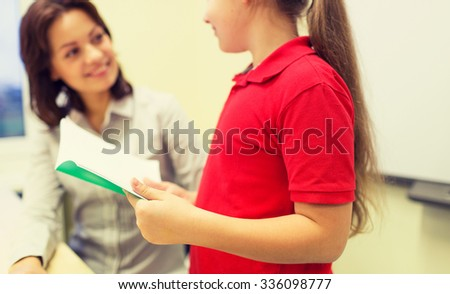 education, elementary school, learning, examination and people concept - close up of school girl with notebook and teacher talking in classroom - stock photo