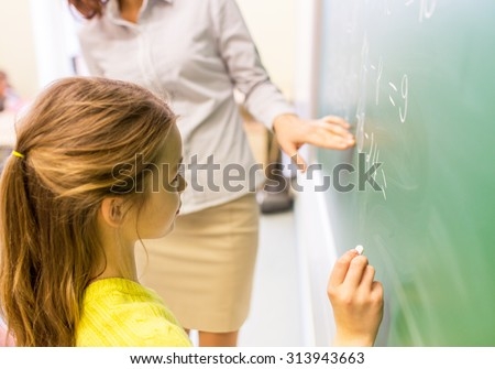 education, elementary school, learning, math and people concept - close up of little schoolgirl with teacher writing on chalk board and solving task at classroom - stock photo