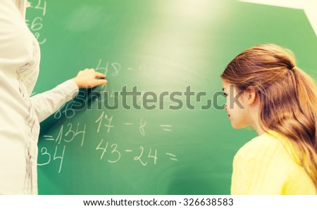 education, elementary school, learning, math and people concept - close up of little schoolgirl with teacher and task on chalk board at classroom - stock photo