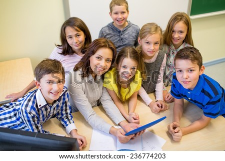 education, elementary school, learning, technology and people concept - group of school kids and teacher with tablet pc computer in classroom - stock photo