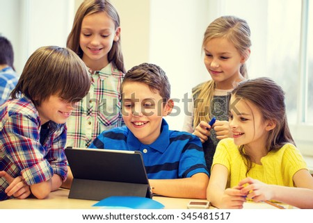 education, elementary school, learning, technology and people concept - group of school kids with tablet pc computer having fun on break in classroom - stock photo