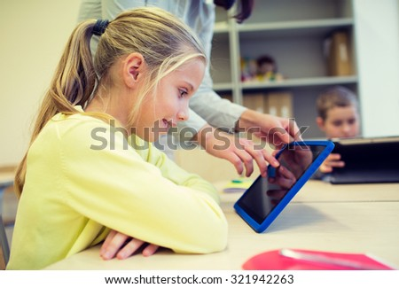 education, elementary school, learning, technology and people concept - little girl with teacher and tablet pc computer in classroom - stock photo