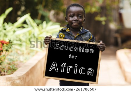 Education for Africa - African Boy Smiling with Blackboard. African boy holding a chalkboard in the streets of Bamako. - stock photo
