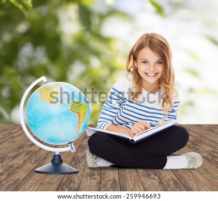education, geography, childhood, people and school concept - little student girl studying with globe and book over green background - stock photo