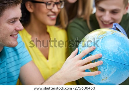 education, geography subject, high school, teamwork and people concept - group of smiling students looking at globe - stock photo