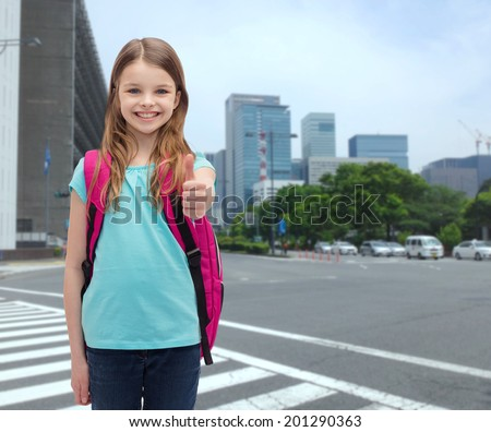 education, gesture and school concept - happy and smiling little girl with school bag showing thumbs up - stock photo