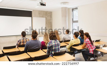education, high school, teamwork and people concept - group of students sitting in lecture hall from back - stock photo