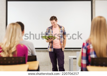 education, high school, teamwork and people concept - smiling student boy with notebook standing and reading in front of students in classroom - stock photo