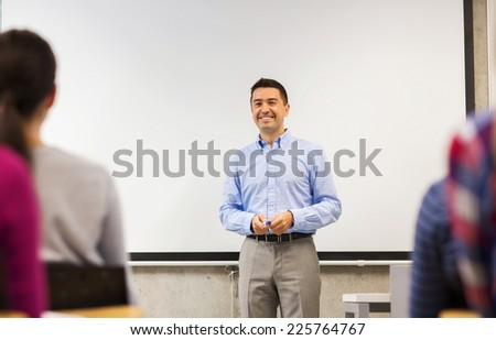 education, high school, teamwork and people concept - smiling teacher standing in front of white board and students in classroom - stock photo