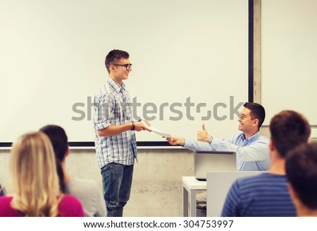 education, high school, technology and people concept - smiling student with notepad, laptop computer standing in front of teacher showing thumbs up gesture in classroom - stock photo