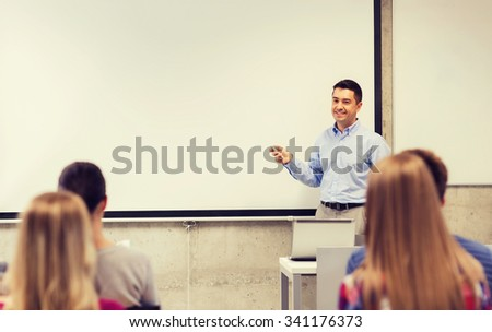 education, high school, technology and people concept - smiling teacher standing with remote control, laptop computer in front of white board and students in classroom - stock photo