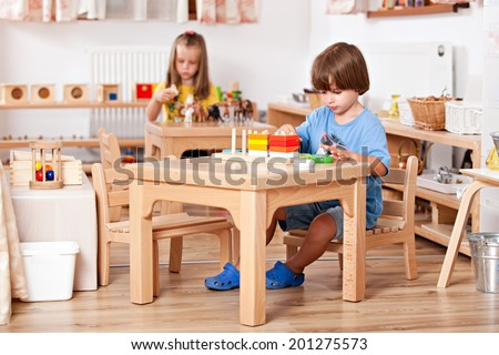 Education image from a kindergarten: child playing with toys at his table - stock photo
