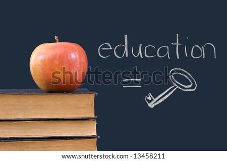 education = key is written on blackboard with apple, books - stock photo