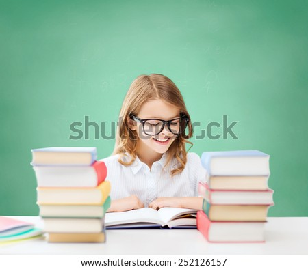 education, people, children and school concept - happy student girl in eyeglasses reading book over green chalk board background - stock photo