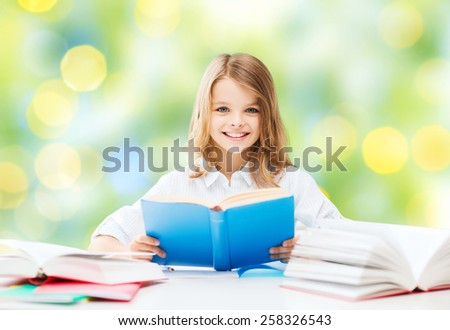 education, people, children and school concept - happy student girl reading book at school over green lights background - stock photo