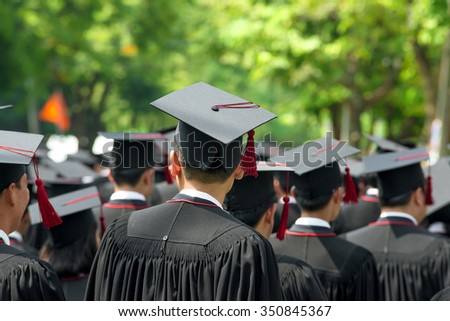 Education, People, Graduate concept - Back of graduates during commencement at university. Close up at graduate cap - stock photo
