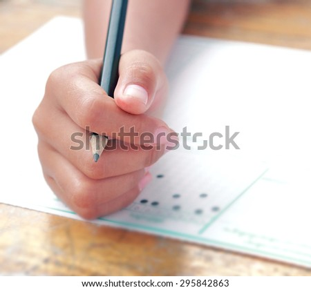 Education person hand on examination answer sheet with black pencil in finger shot with wide aperture - stock photo