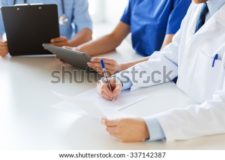 education, profession, people and medicine concept - close up of happy doctors with tablet pc computer and papers at seminar or hospital - stock photo