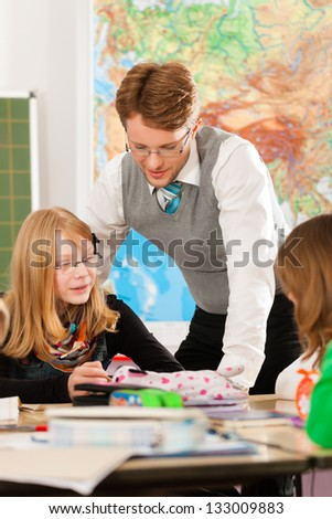 Education - Pupils and teacher learning at elementary or primary school in the classroom - stock photo