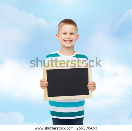 education, school, advertisement and people concept - smiling little boy holding blank black chalkboard over blue cloudy sky background - stock photo