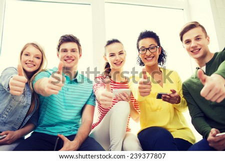 education, school and technology concept - smiling students with smartphone texting at school - stock photo