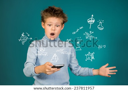 Education school and technology concept. Surprised boy with smartphone on blue background. - stock photo