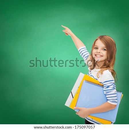 education, school and virtual screen concept - cute little girl with colorful folders pointing in the air or virtual screen - stock photo
