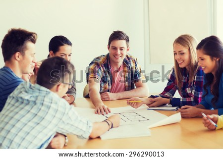 education, school, architecture and people concept - group of smiling students with blueprint meeting indoors - stock photo