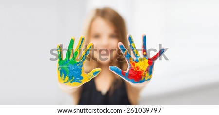 education, school, art and painitng concept - little student girl showing painted hands - stock photo