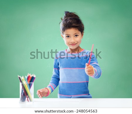 education, school, children, creativity and happy people concept - happy little girl drawing with coloring pencils over green chalk board background - stock photo