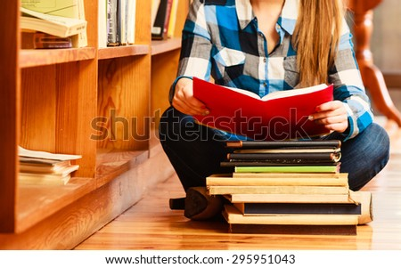 Education school concept. Clever female student girl sitting on floor in college library with stack books reading. Indoor - stock photo