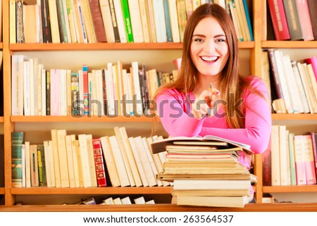 Education school concept. Happy female student fashion long hair girl in college library with stack books making research pointing with pen - stock photo