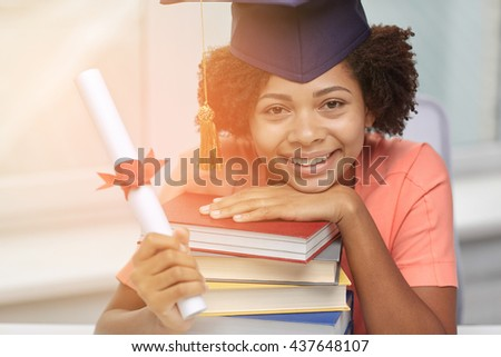 education, school, graduation and people concept - happy smiling african american student girl in bachelor cap with books and diploma sitting at table at home - stock photo