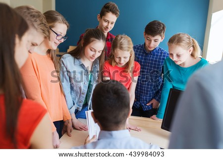 education, school, learning, teaching and people concept - group of students and teacher talking in classroom - stock photo