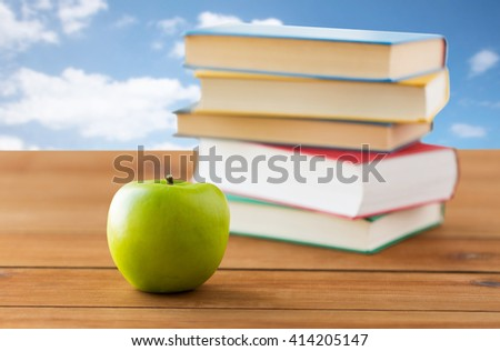 education, school, literature, reading and knowledge concept - close up of books and green apple on wooden table over blue sky and clouds background - stock photo