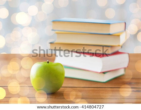 education, school, literature, reading and knowledge concept - close up of books and green apple on wooden table over holidays lights background - stock photo