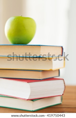 education, school, literature, reading and knowledge concept - close up of books and green apple on wooden table - stock photo