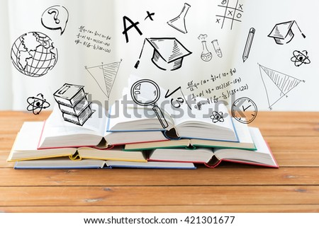 education, school, literature, reading and knowledge concept - close up of books on wooden table over school doodles - stock photo