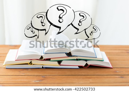 education, school, literature, reading and knowledge concept - close up of books on wooden table and question marks - stock photo