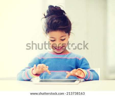 education, school, technology and internet concept - little student girl with tablet pc at home - stock photo